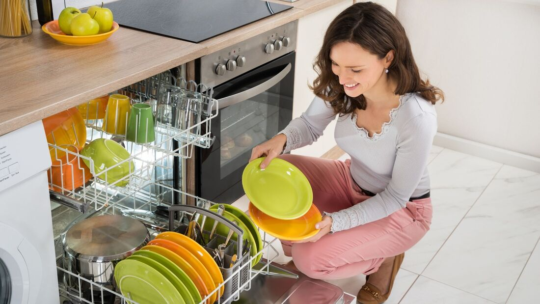 woman taking clean dishes from the dishwasher